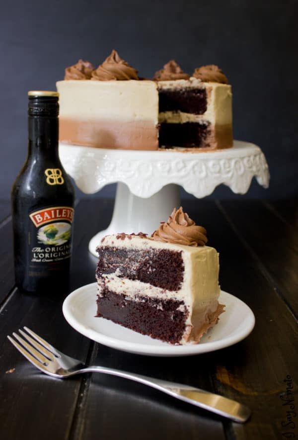 Slice of cake on plate with whole cake on cake stand next to bottle of Baileys