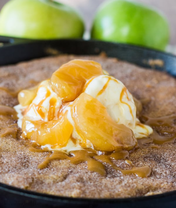 Caramel Apple Stuffed Snickerdoodle Skillet Cookie in cast iron skillet topped with ice cream, apples and caramel