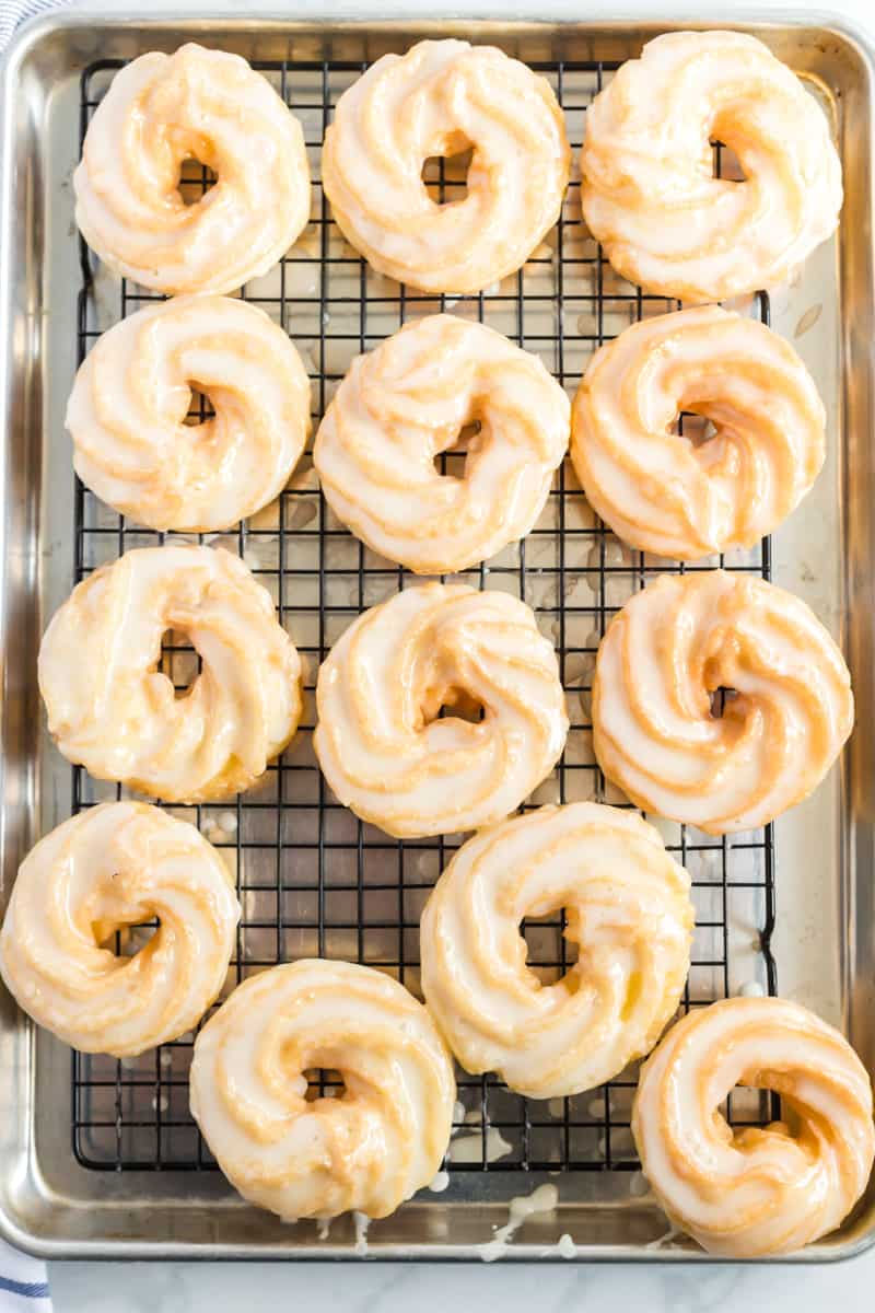 Crullers on wire rack lined baking sheet with glaze dripping off