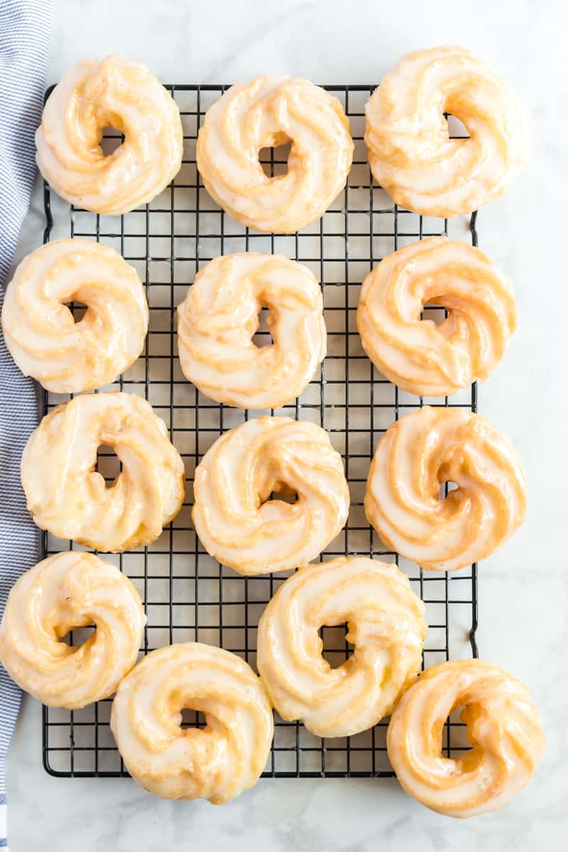 finished French crullers on cooling rack with glaze setting up
