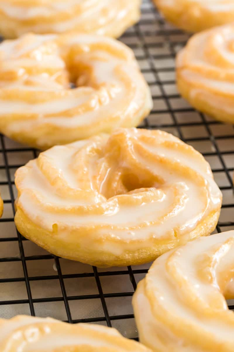 Close up of glazed French Cruller on cooling rack