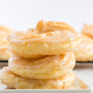 Three Crullers stacked on top of one another on white square plate