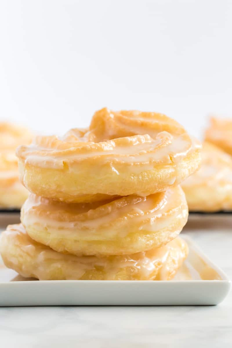 Stacked and glazed crullers on plates