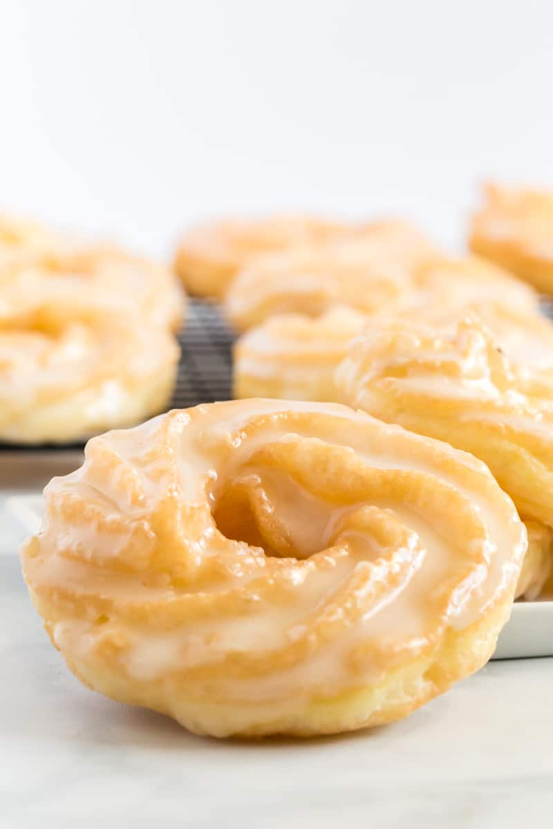 Close up of finished cruller recipe glazed and leaning against other crullers