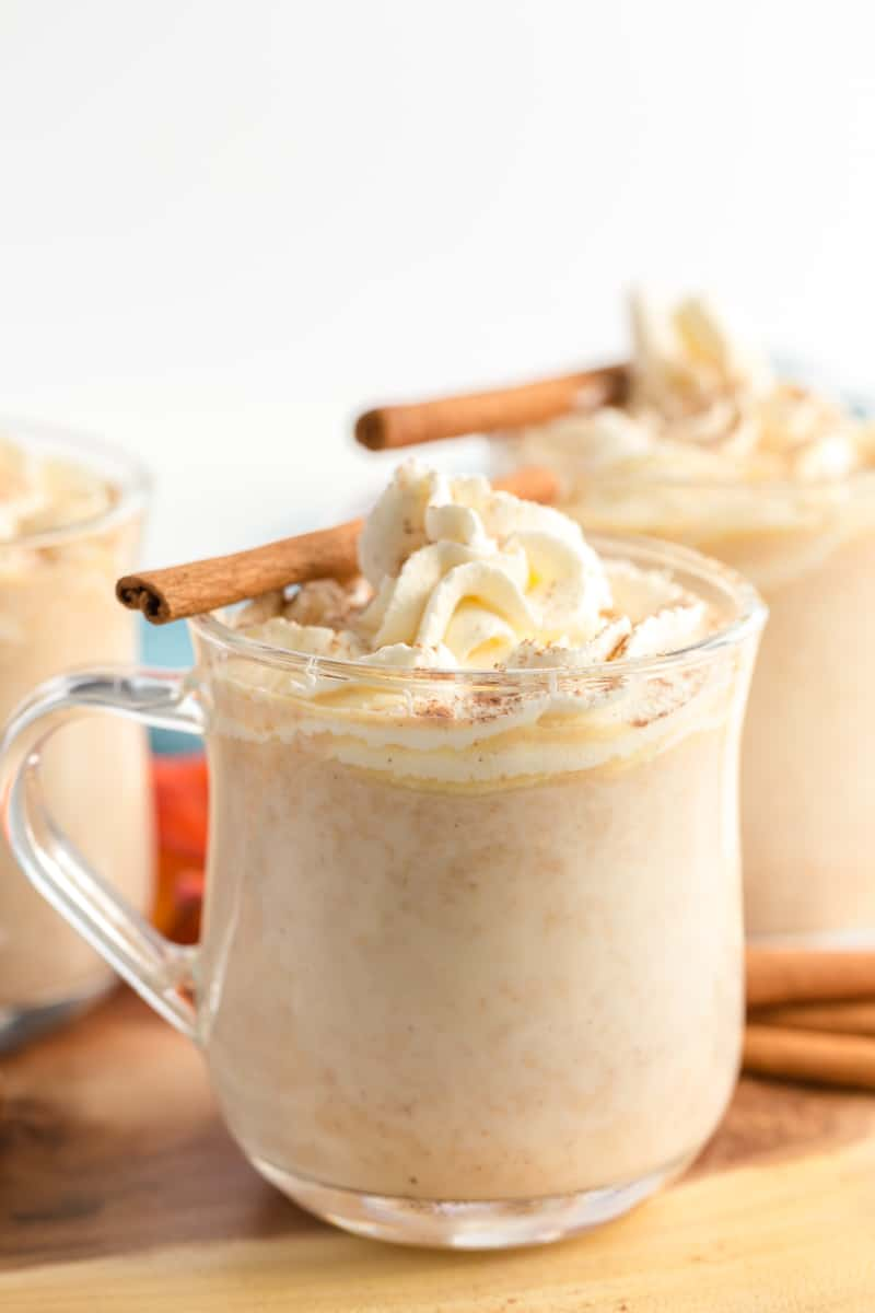 3 mugs of pumpkin hot chocolate on wooden board with whipped cream and cinnamon sticks