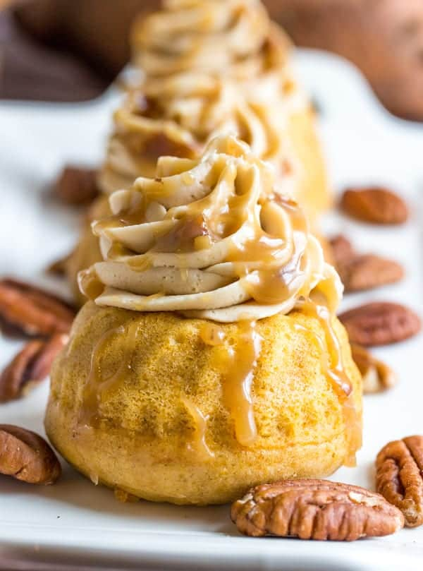 Sweet Potato Bourbon Mini Bundt Cakes on white platter with frosting and caramel