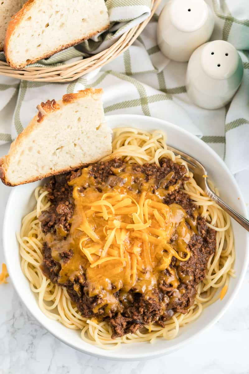 Chili plated in bowl with melted cheese and slice of bread with bread basket on side