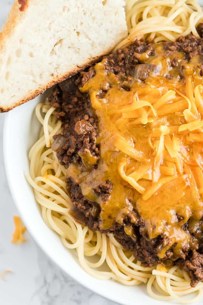 Overhead photo of Cincinnati Chili in bowl with melted cheese and a slice of bread