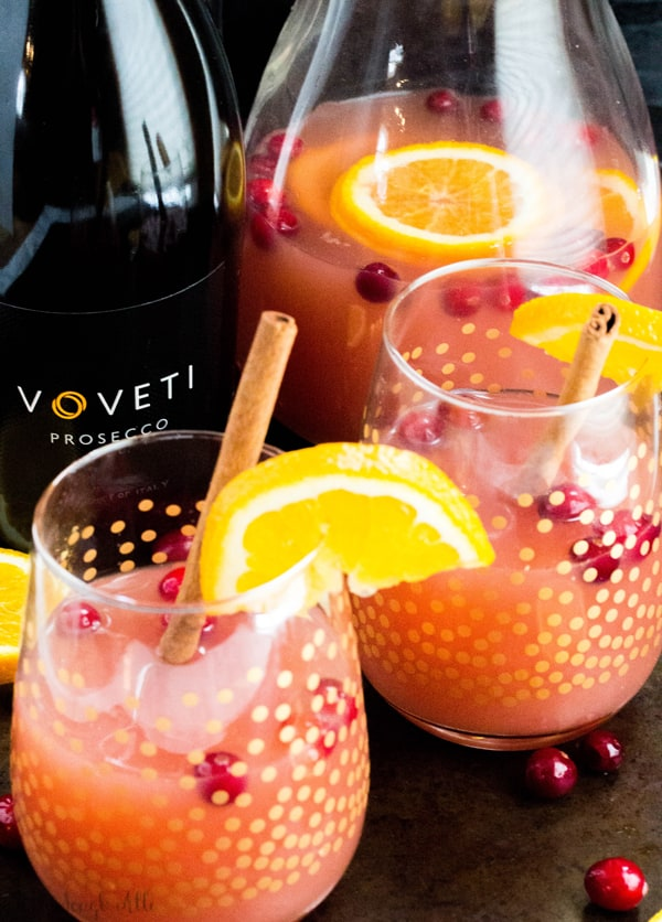 Overhead of Cranberry Orange Mimosas in glasses next to prosecco bottle