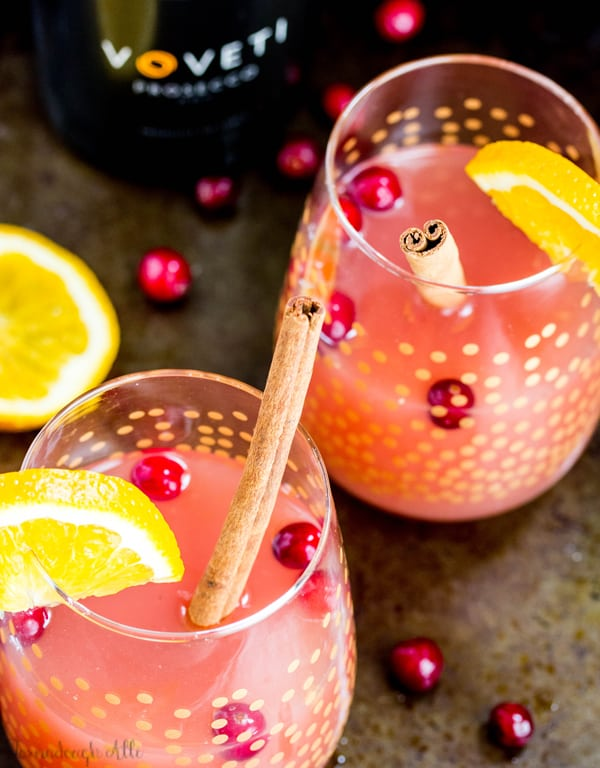 Overhead photo of Cranberry Orange Mimosas in two glasses with barges and cinnamon sticks