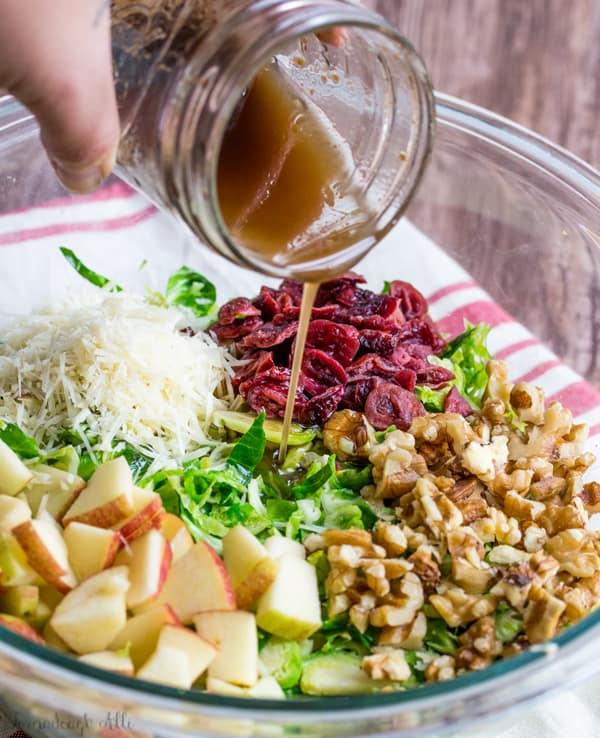 Sauce being pour over Shredded Brussel Sprout Harvest Salad ingredients