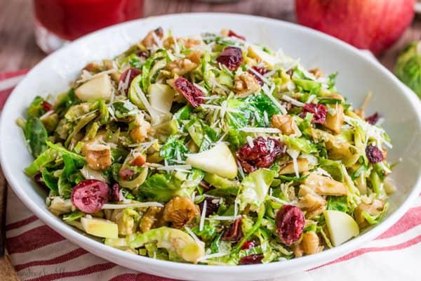Shredded Brussel Sprout Harvest Salad horizontal image in white bowl
