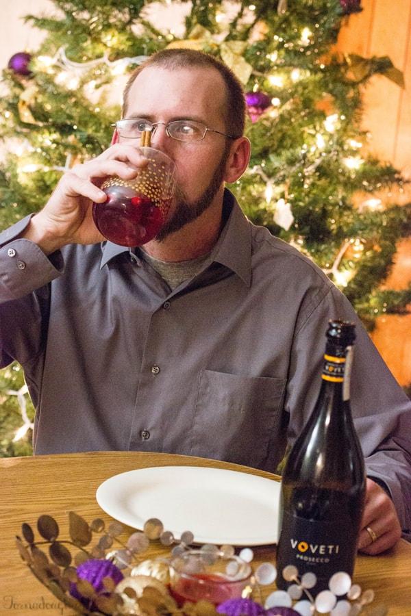 Husband drinking glass of Cranberry Orange Mimosa