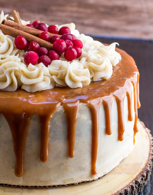 Gingerbread Cake with Cinnamon Cream Cheese Frosting and Caramel Drizzle on wooden round