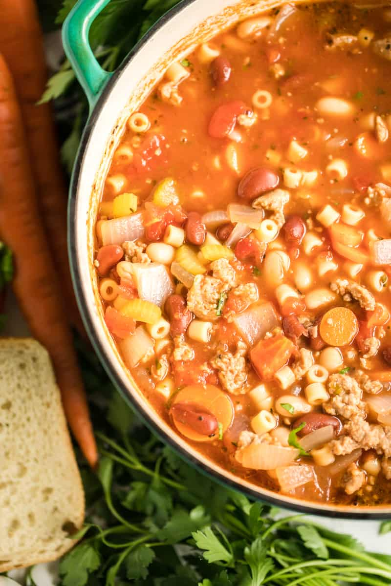Cooked Pasta e Fagioli Soup in pot surrounded by herbs and carrots