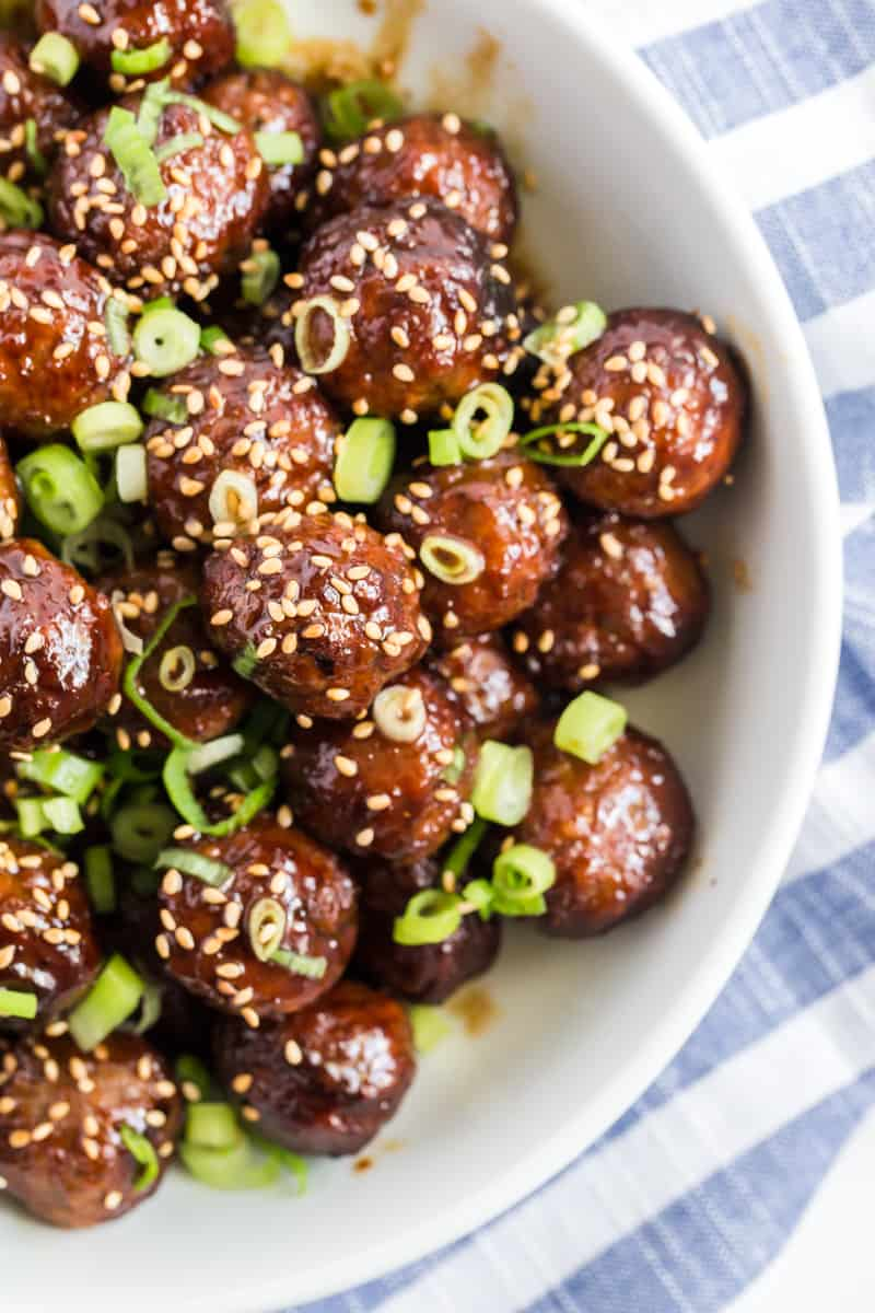 Crockpot Meatballs in bowl slathered in sauce and topped with sesame seeds and green onions