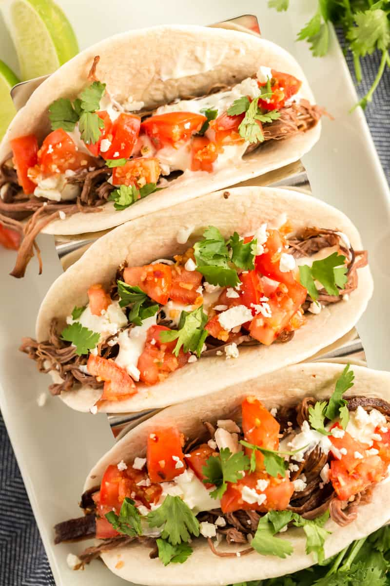 Overhead photo of Slow Cooker Street Tacos topped with pico de Gallo, cheese and cilantro