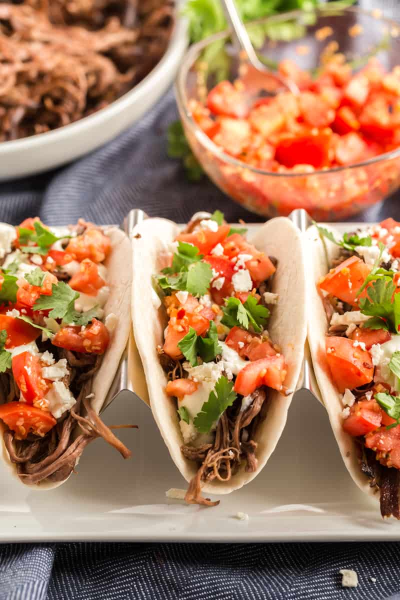 Close up of street tacos on plate with layers of shredded beef, cheese, pico de Gallo and cilantro