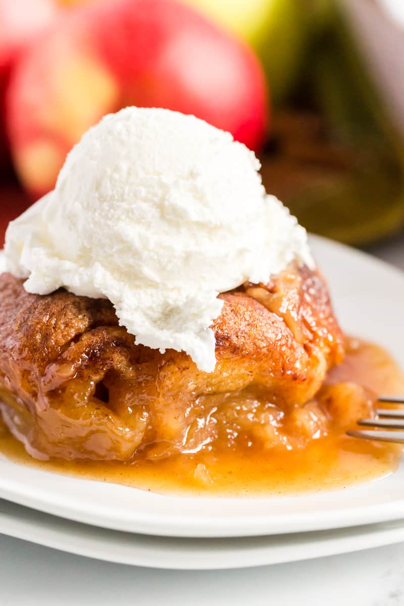 Apple Dumplings on plate with ice cream on top and apples in background
