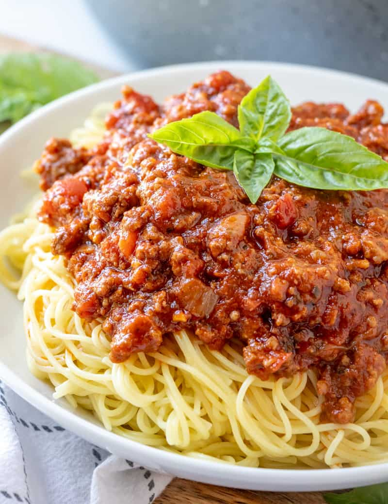 Close up of easy homemade spaghetti sauce served over spaghetti with basil leaves on top