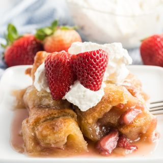Strawberry Dumplings on plate topped with whipped cream and sliced strawberries