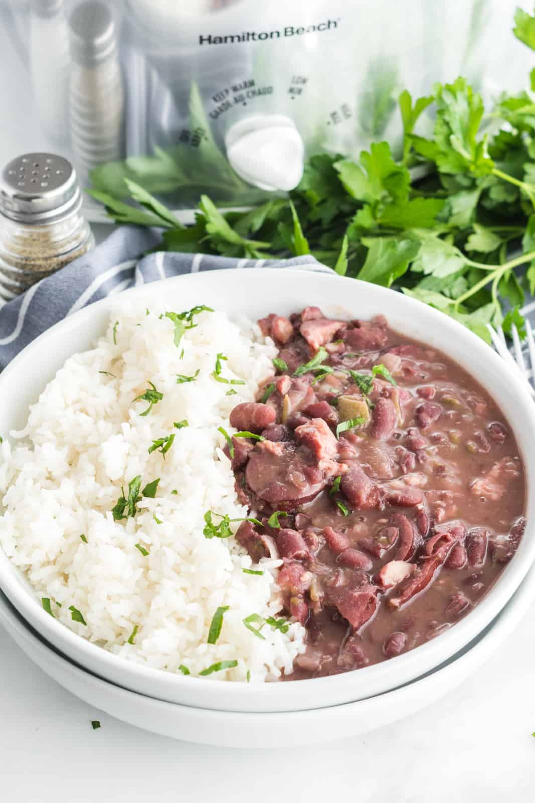 Red beans in rice in bowl with slow cooker and parsley in background