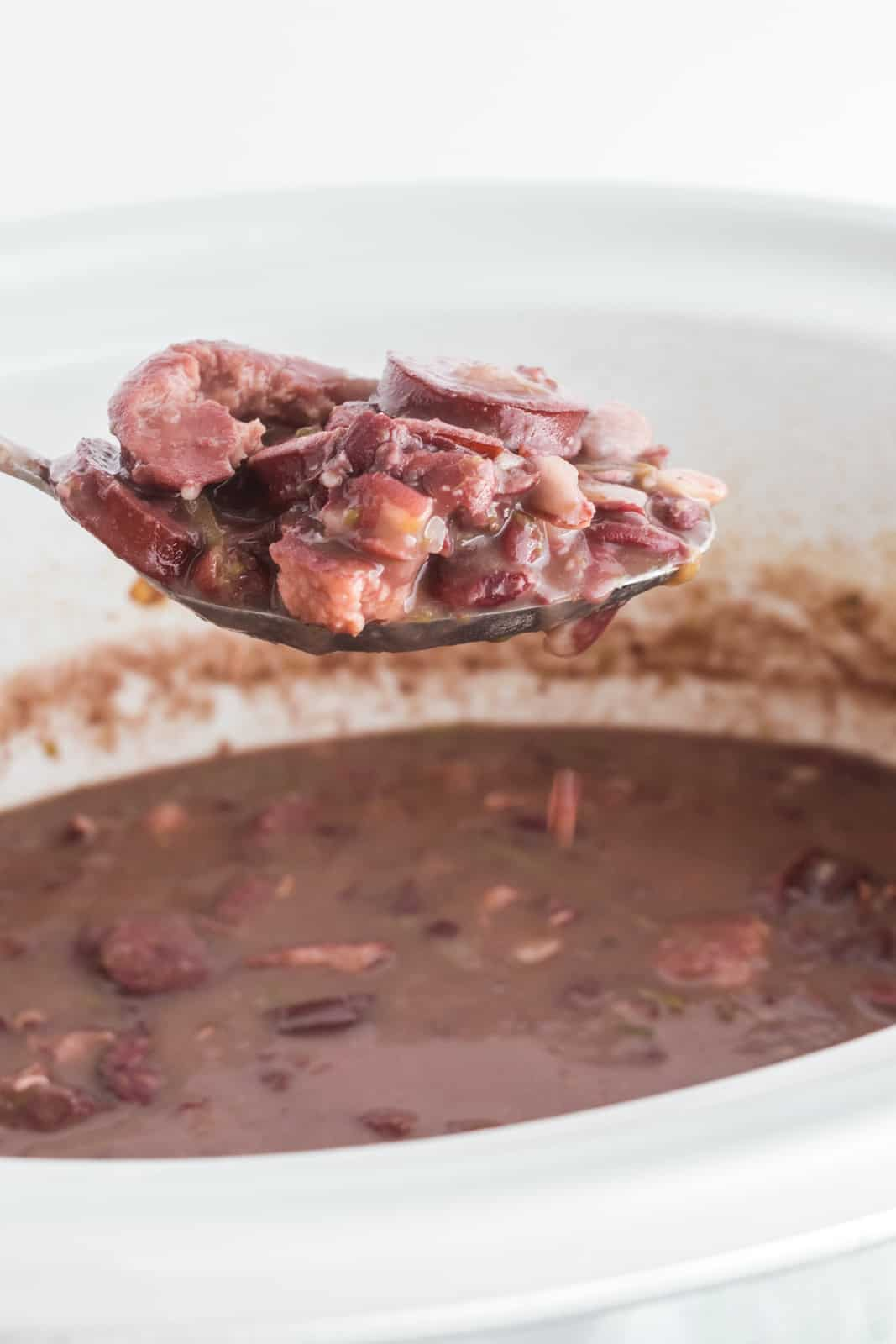 Spoon scooping red beans and rice out of slow cooker