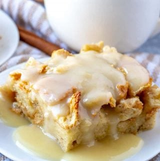 Slice of bread pudding on white plated drizzled with vanilla sauce