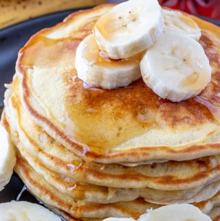 Plated pancakes stacked on top of one another with syrup and sliced bananas
