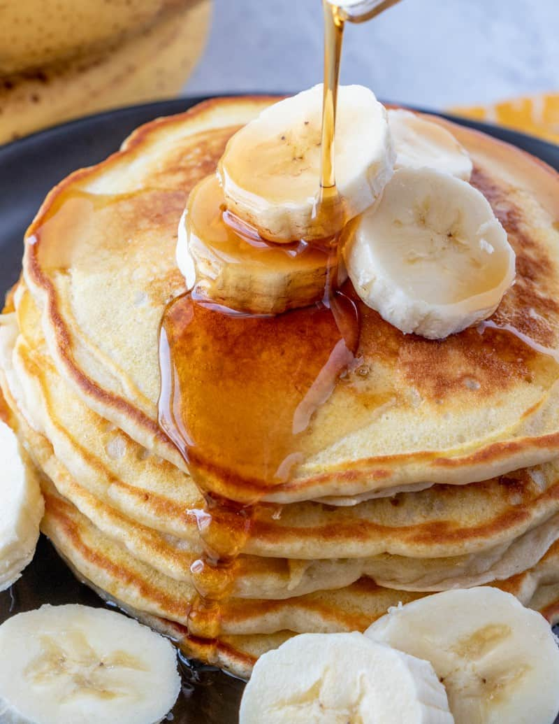 Banana pancakes with syrup being poured over top