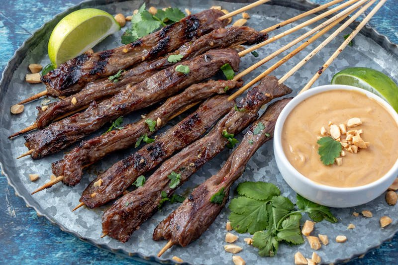 Beef Satay on trap horizontal image with dipping sauce