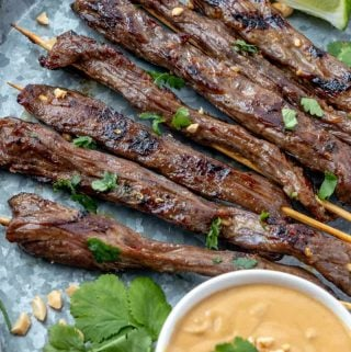 Skewers of satay on galvanized tray garnished with cilantro