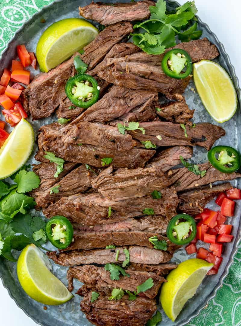Carne asada on tray above shot with limes, jalapeños, tomatoes and cilantro