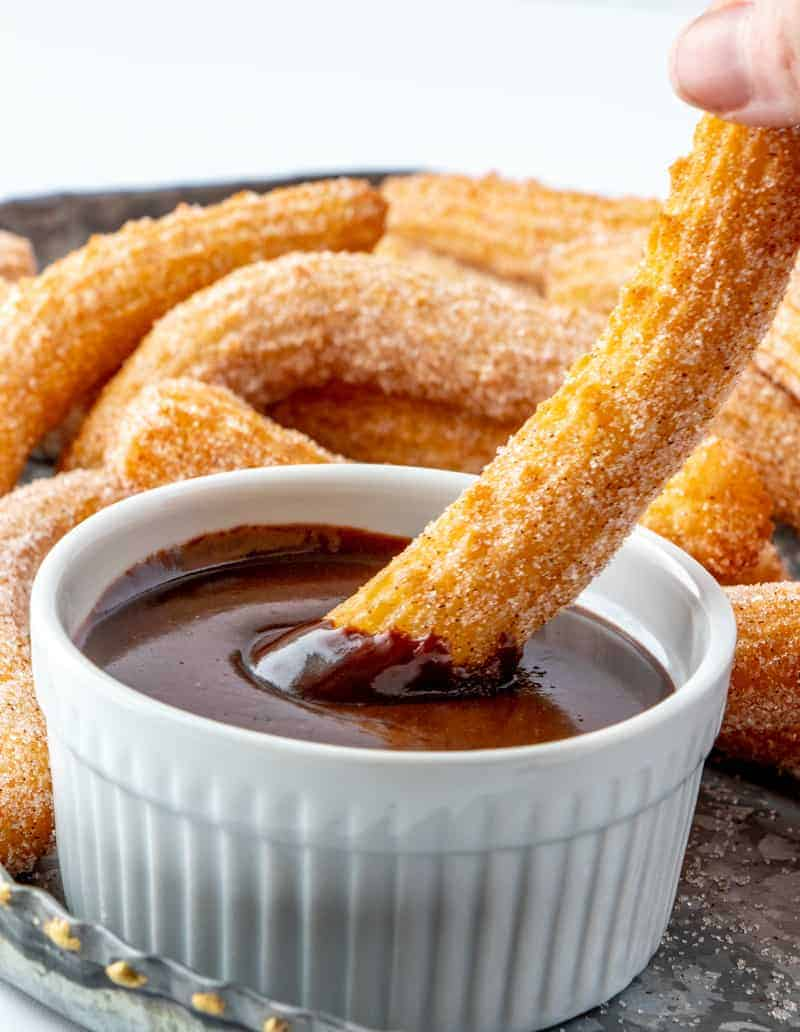Churro being dipped in chocolate dipping sauce