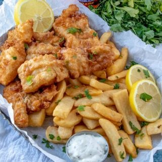 Tray of fish and chips with lemon slices and parsley