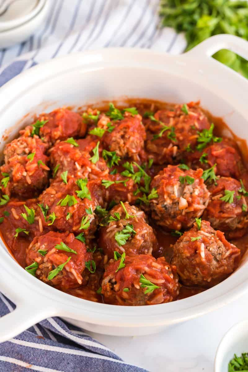 Side view of finished baked meatballs topped with parsley