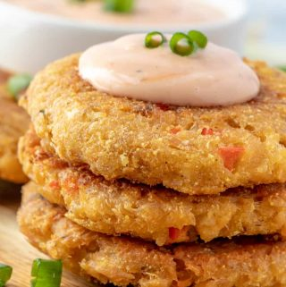 Three stacked salmon patties topped with sauce and green onions