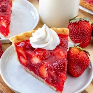 whipped cream topped strawberry pie with strawberry next to slice.