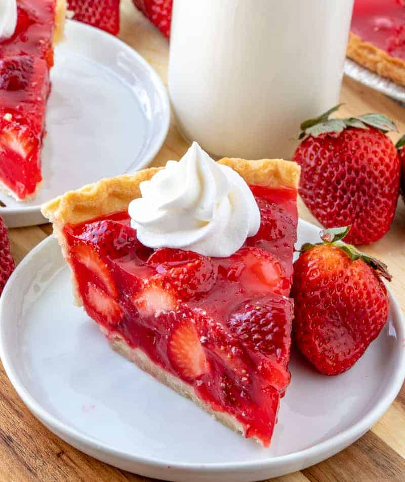 Strawberry pie on plate with whipped cream and milk on side