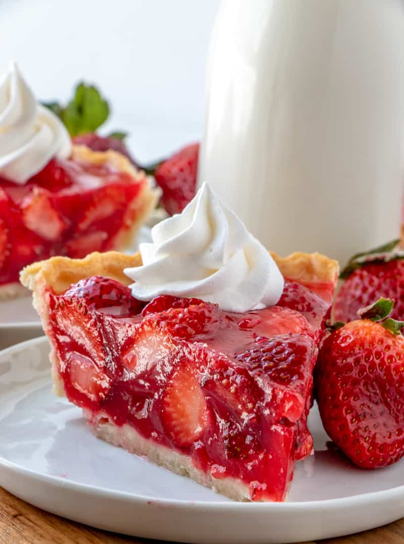 Close up photo of side of strawberry pie with whipped cream
