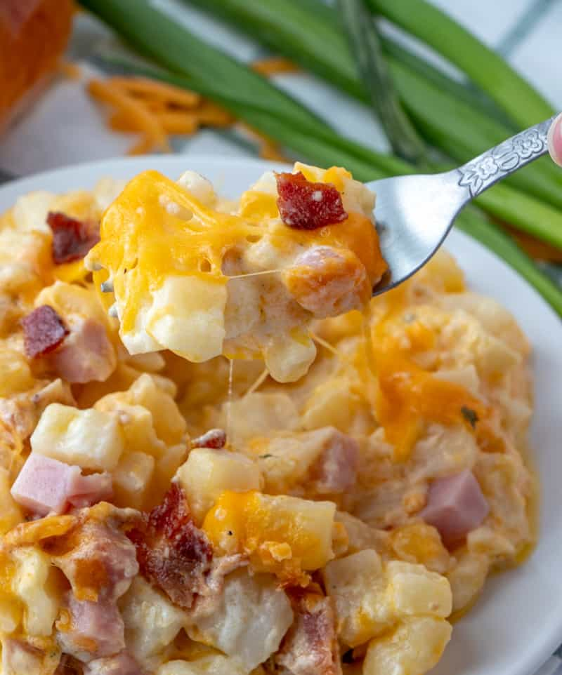 Forkful of Ham & Bacon Cheesy Potatoes with strands of cheese