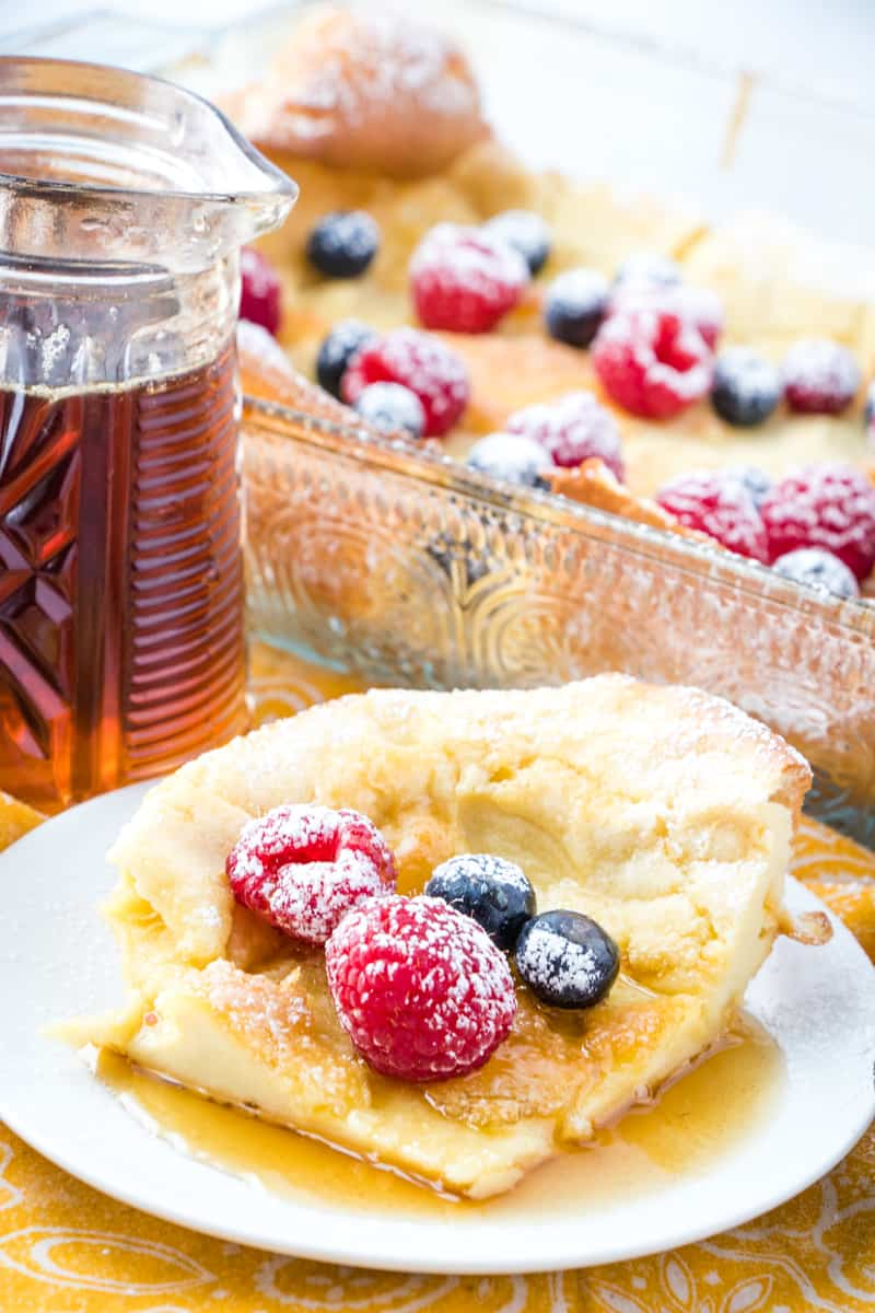 Slice of German Pancake on plate with berries and syrup
