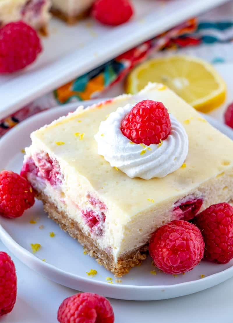 Lemon Raspberry Cheesecake bars on plate topped with whipped cream and raspberry