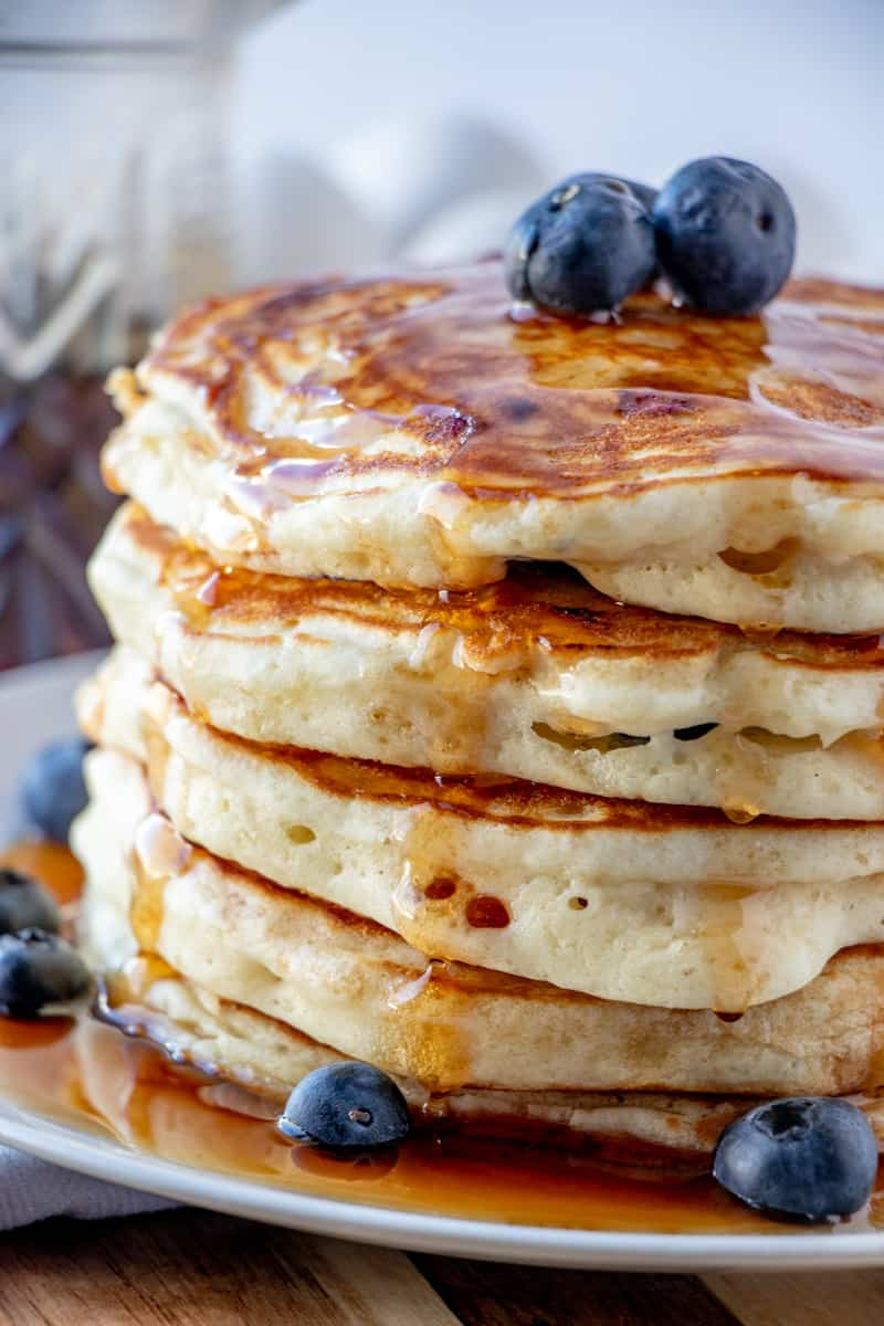 Side shot of blueberry pancakes on plate with syrup dripping down