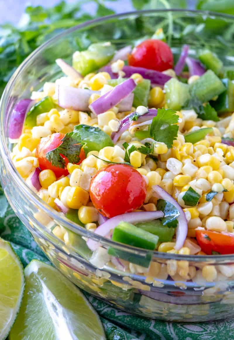 Corn salad in bowl with lime wedges next to it