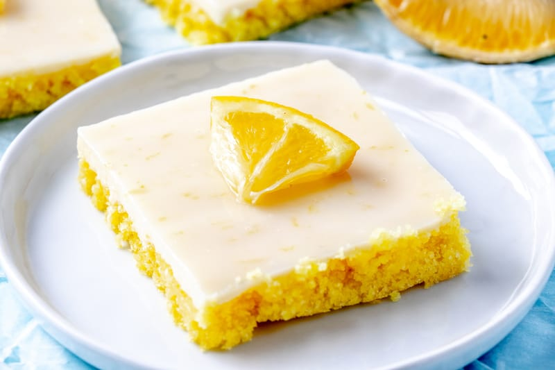 Horizontal photo of lemon squares with slice of lemon on top