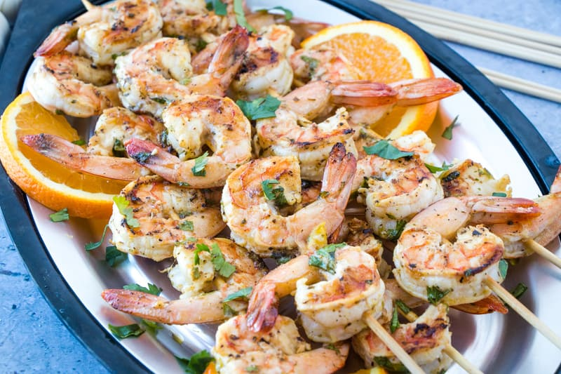 Mojo Shrimp Kabobs horizontal photo on plate with orange slices