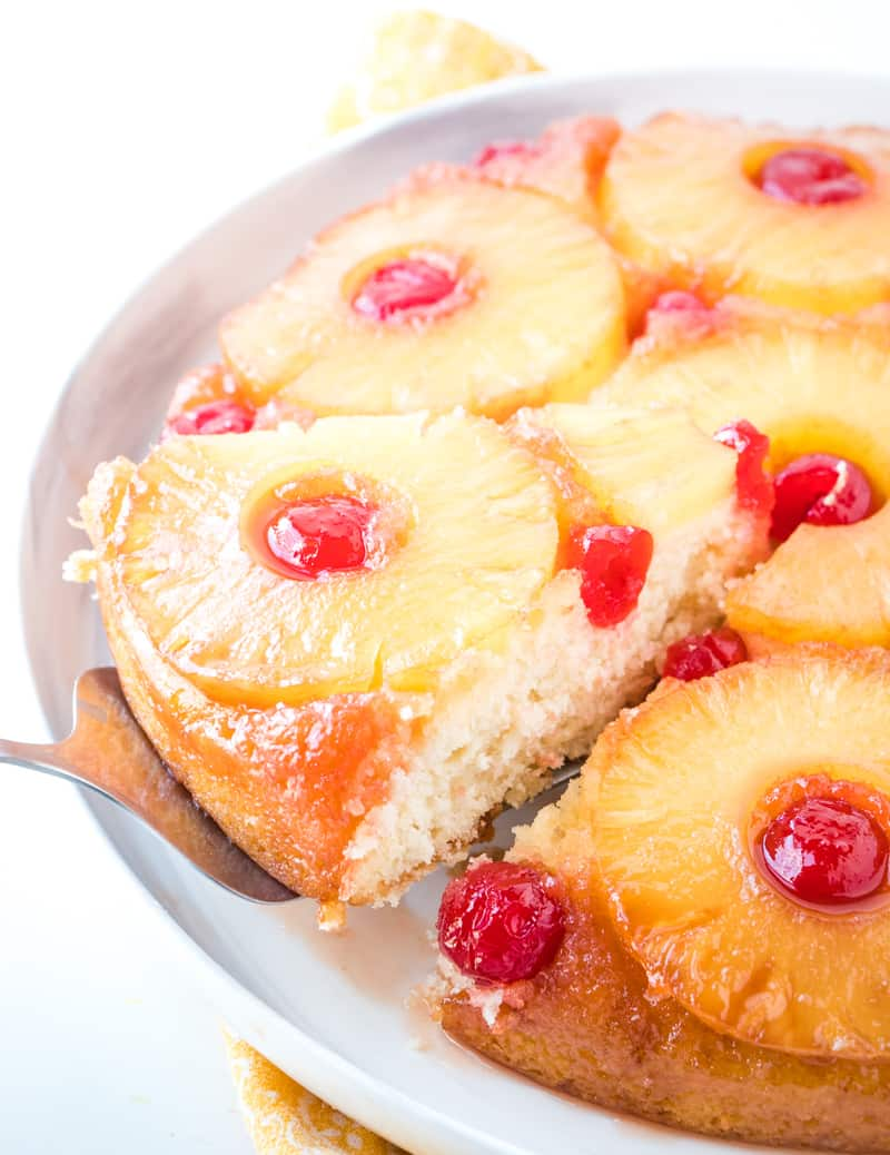 Pineapple upside down cake recipe on plate with slice on cake server