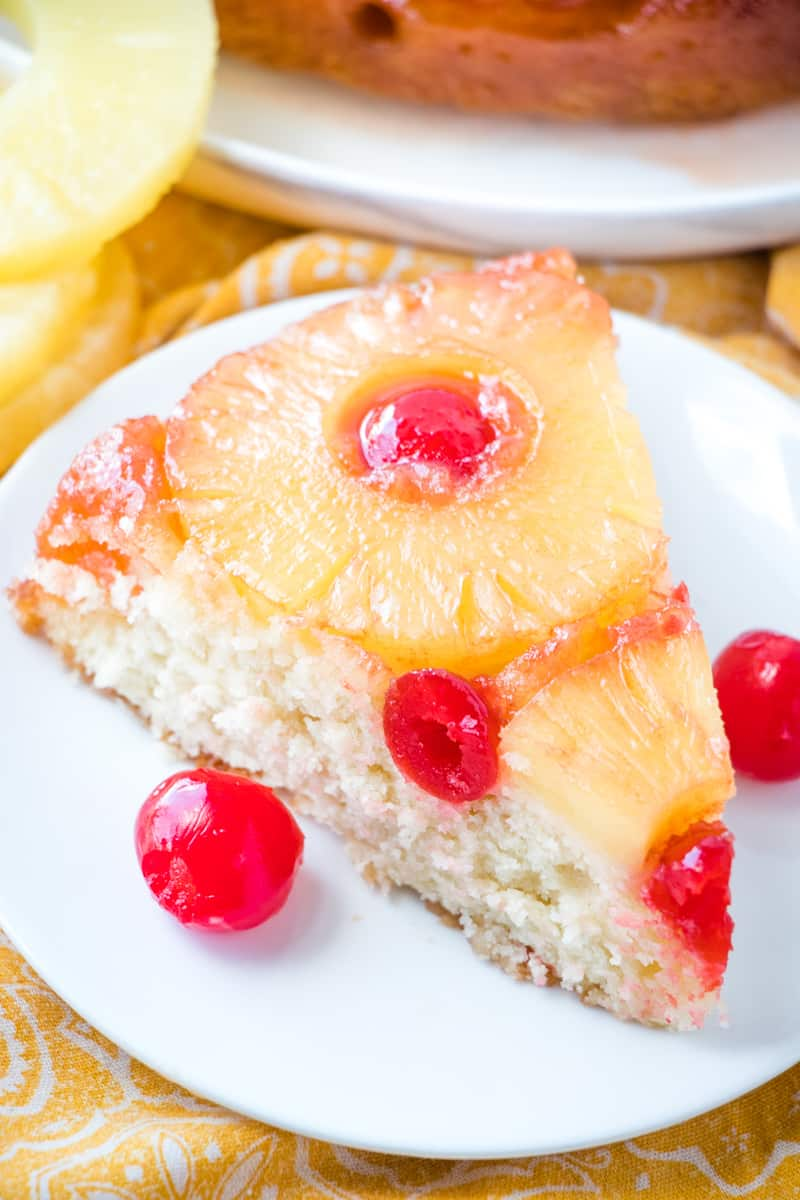 Close up photo of Pineapple Upside Down Cake recipe on plate with cherries