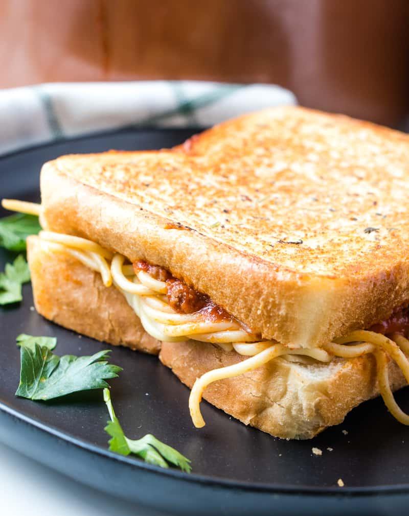 Spaghetti sandwich on black plate uncut